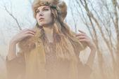 Fille en manteau de fourrure, posant au fond de branches — Photo