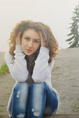 Beauty girl looking to camera sitting on asphalt — Stockfoto
