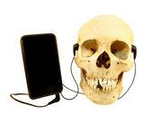 Human skull listening music — Stock Photo
