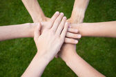 Arms uniting above grass — Stock Photo