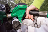 Hand with hose filling car tank with gasoline — Stock Photo