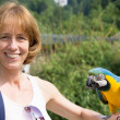 Woman with blue-and-yellow macaw on her arm — ストック写真