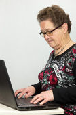 Elderly woman working at a laptop — Stock Photo