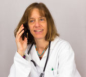 Female doctor phones with mobile phone — Stok fotoğraf