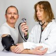 Doctor checks blood pressure of a patient — Stock Photo #47385969