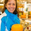 Woman showing round cheese — Stock Photo