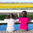 Girl and boy looking through fence at flower field — Stock Photo
