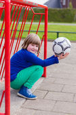 Young crouching girl with ball in red metal goal — Stok fotoğraf