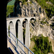 Bernina Express, swiss red train passing over a Viaduct high in the Alps in Switzerland. Bernina line is the highest railway in Europe. — Stock Photo #31553409