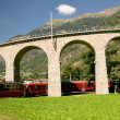 Bernina Express in Brusio Switzerland. Train is passing under bridge arch. — Stock Photo #31553415