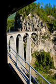 Bernina Express, swiss red train passing over a Viaduct high in the Alps in Switzerland. Bernina line is the highest railway in Europe. — Stock Photo