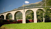 Bernina Express in Brusio Switzerland. Train is passing under bridge arch. — Stock Photo