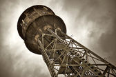Water tower under dark clouds — Stock Photo
