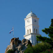 White church tower and greek flag against blue sky — Stock Photo