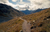 Rocky trail leading to valley surrounded by high mountains in Swiss Alps — Stock Photo