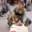 Tapestry tradesman sitting in the middle of crowded street in bazaar market. Iraq. Middle East. — Stock Photo