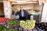 Grocer greets his client standing behind his vegetables in small shop in Bazaar. Halabja, Iraq, Middle East. — Stock Photo