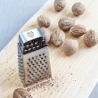 Nutmeg on wooden chopping board with tiny grater. — Стоковая фотография