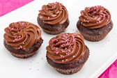 Chocolate cupcakes with pink coconut sprinkles — Stock Photo