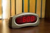Digital clock on the bookshelf — Stock Photo