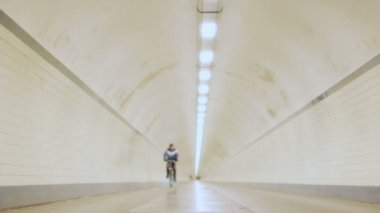 Cyclist Rolls Out in Long Lit Up Tunnel in Slow Motion — Stock Video