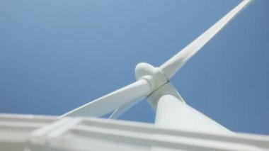 Turbine windmolen in focus achter reling van metalen trap onder de blauwe hemel — Stockvideo