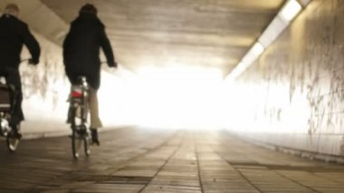 Three Cyclists Cycling into the Light at the End of the Tunnel — Stock Video