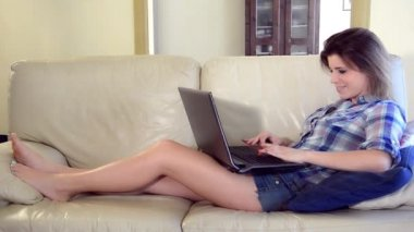 Cute girl chatting on her laptop lying on the sofa — Stock Video