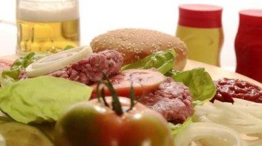 Raw burgers, beer, mustard and ketchup — Stock Video