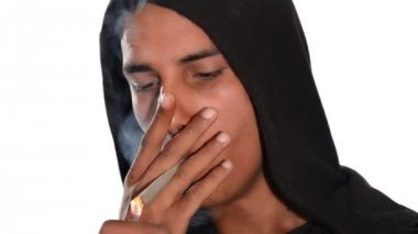 Close up of young man smoking hashish joint on white background. — Stockvideo