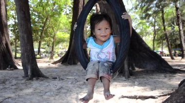 Thai child on a tire swing — Stock Video