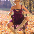 Autumn portrait of young pretty woman on a vintage chair — Stock Photo