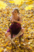 Sexy girl on a vintage chair among autumn leaves — Stock Photo