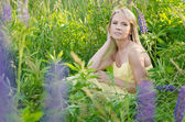 Young beautiful woman in the lupine field — Stock Photo