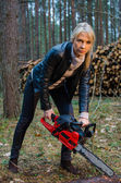 Young pretty woman with huge red chainsaw — Stock Photo
