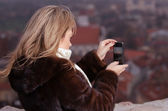 Young woman photographing city of Vilnius — Stock Photo