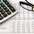 Financial reports with calculator and glasses — Stock Photo