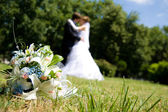 Bunch of white roses and newly-weds — Stock Photo