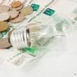 The bulb and is a lot of coins — Stock Photo #30992179