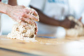 A Caucasian woman next to an African one kneading — Stock Photo