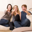 Stock Photo: Group of happy teenagers on sofpointing