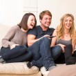 Three teenagers enjoy a funny television program — Zdjęcie stockowe #39869871