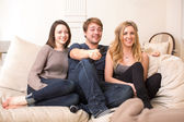 Three teenage friends sitting watching television — Stock Photo