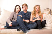 Fascinated teenagers sitting watching television — Stock Photo