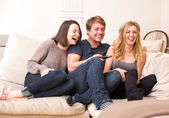 Three teenagers enjoy a funny television program — Stock Photo
