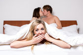 Cheeky young woman in a threesome in bed — Stockfoto