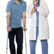 Man using crutches, next to a friendly physician — Stock Photo #47507529