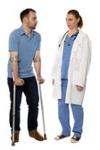 Man on crutches consulting with a doctor — Stock Photo