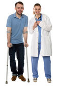 Man using crutches, next to a friendly physician — Stock Photo
