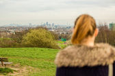 Woman looking out over countryside to a town — Stockfoto